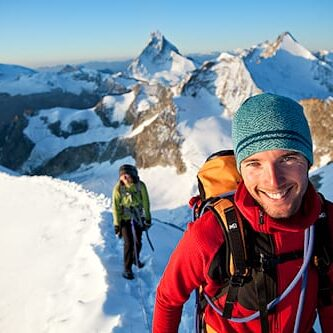 Portrait of a smiling alpine climbing guide with client in the Swiss Alps